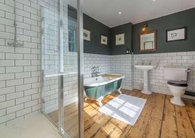 Modern shower cubicle and free standing bath in Gardener's Cottage bathroom in Norfolk