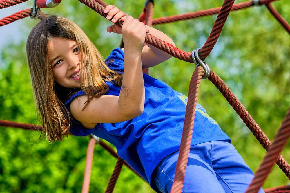 Young girl having fun on climbing frame