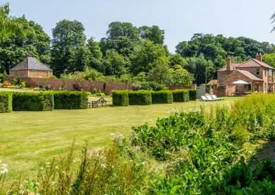Image shows the lawn and shrubbery of one edge of the walled garden at Fring Estate